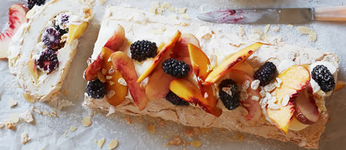Rolled pavlova with peaches and blackberries
