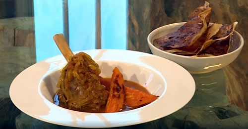 Braised lamb shanks with roasted sweet potatoes and spiced crisps