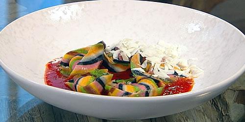 Multi-coloured ravioli with tomato sauce